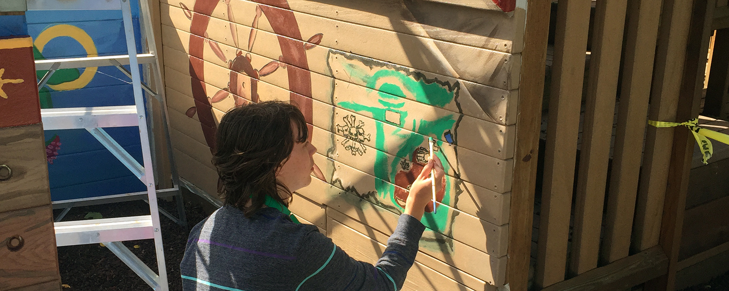 A Prairie Phoenix Academy Student Creates The Pirate Ship Mural At The Playground.